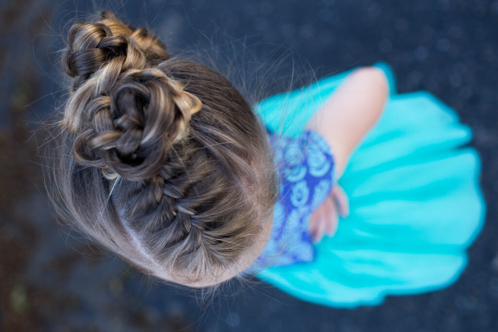 "Top view of a little girl with long hair standing outside modeling ""Triple Bun Updo"" hairstyle"