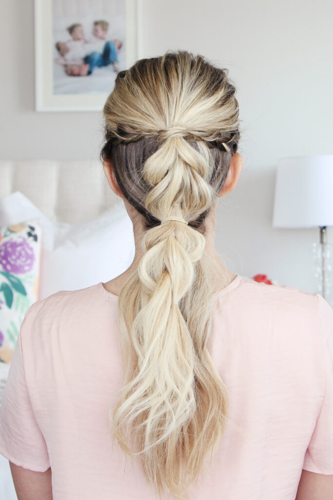 """Back view of young woman standing in her room wearing pink shirt modeling """"4-in-1 Pull Thru Braid"""" Hairstyle"""