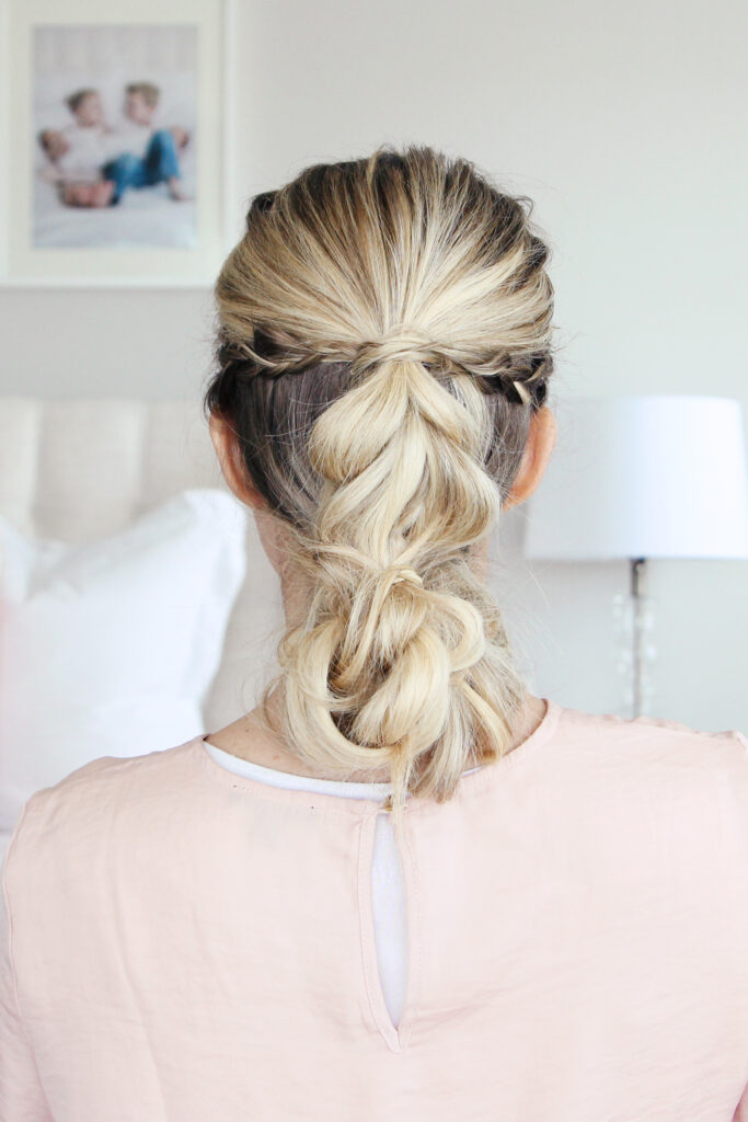 """Close up back view of young woman standing in her room wearing pink shirt modeling """"4-in-1 Pull Thru Braid"""" Hairstyle"""
