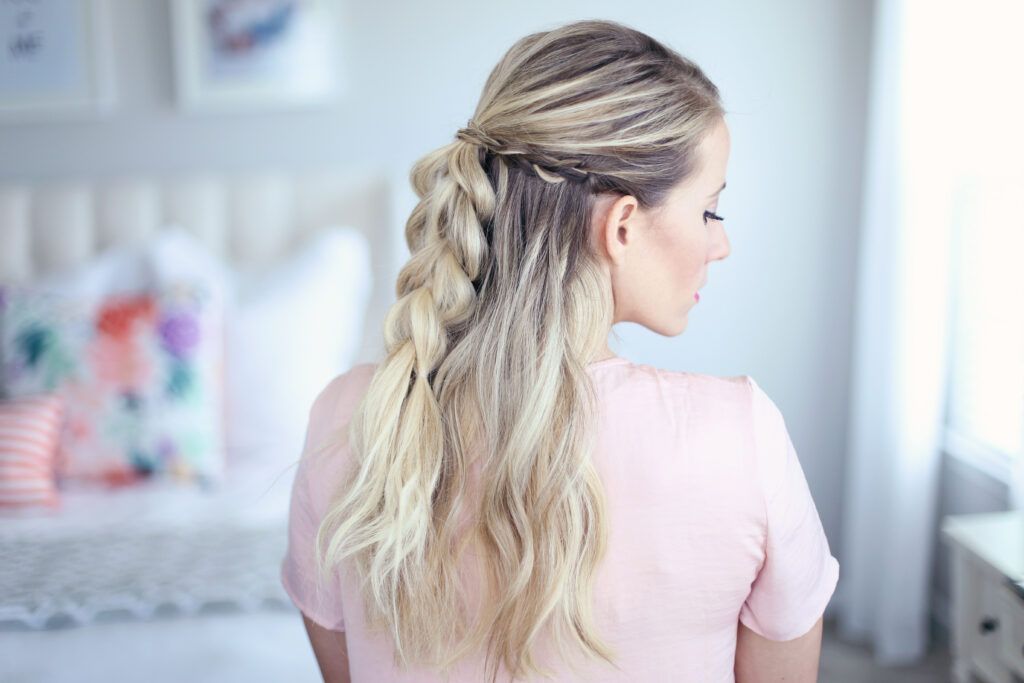 """Side view of young woman standing in her room wearing pink shirt modeling """"4-in-1 Pull Thru Braid"""" Hairstyle"""