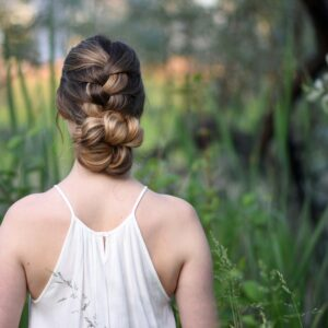 "Back view of girl with a white dress standing outside in greenery and modeling ""Knotted Braid Updo"" hairstyle."