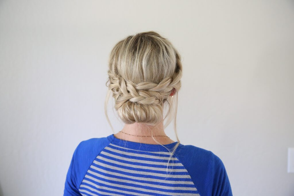 """Back view of woman standing in front of a white background with a blue shirt modeling """"French Lace Updo"""" hairstyle"""