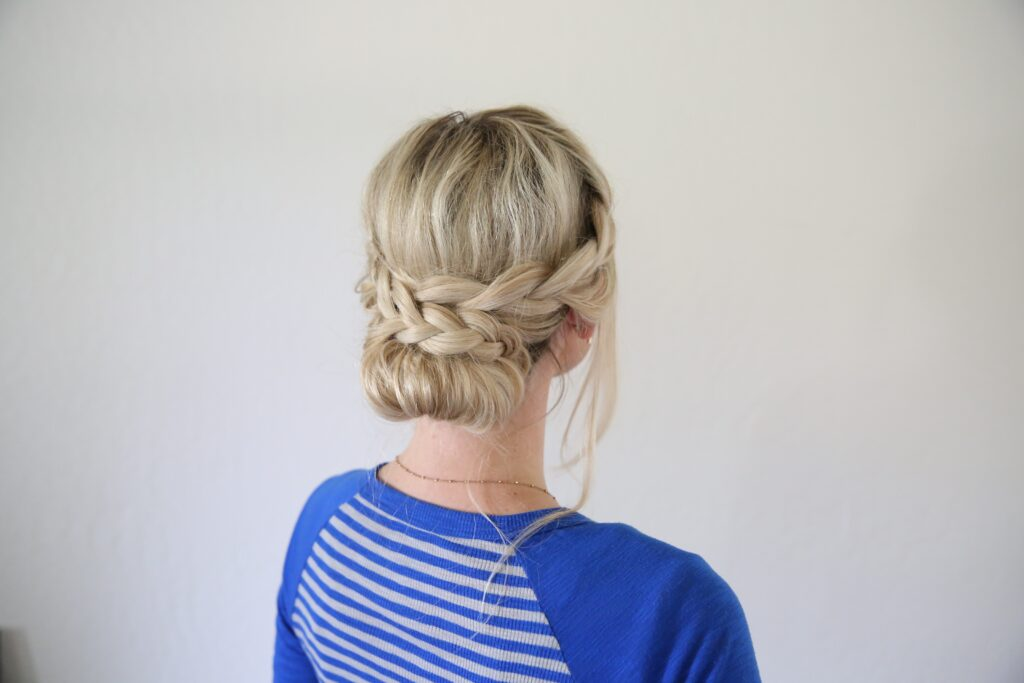 """Side view of woman standing in front of a white background with a blue shirt modeling """"French Lace Updo"""" hairstyle"""