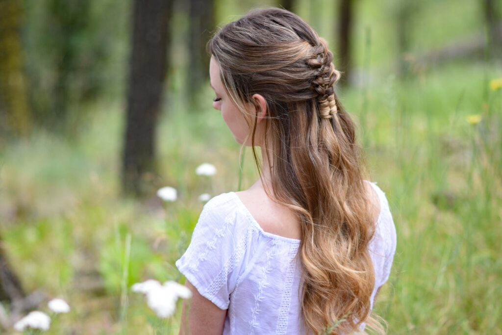 "Side view of young girl standing in a meadow wearing a white shirt modeling ""Floating Infinity Braid"" hairstyle"