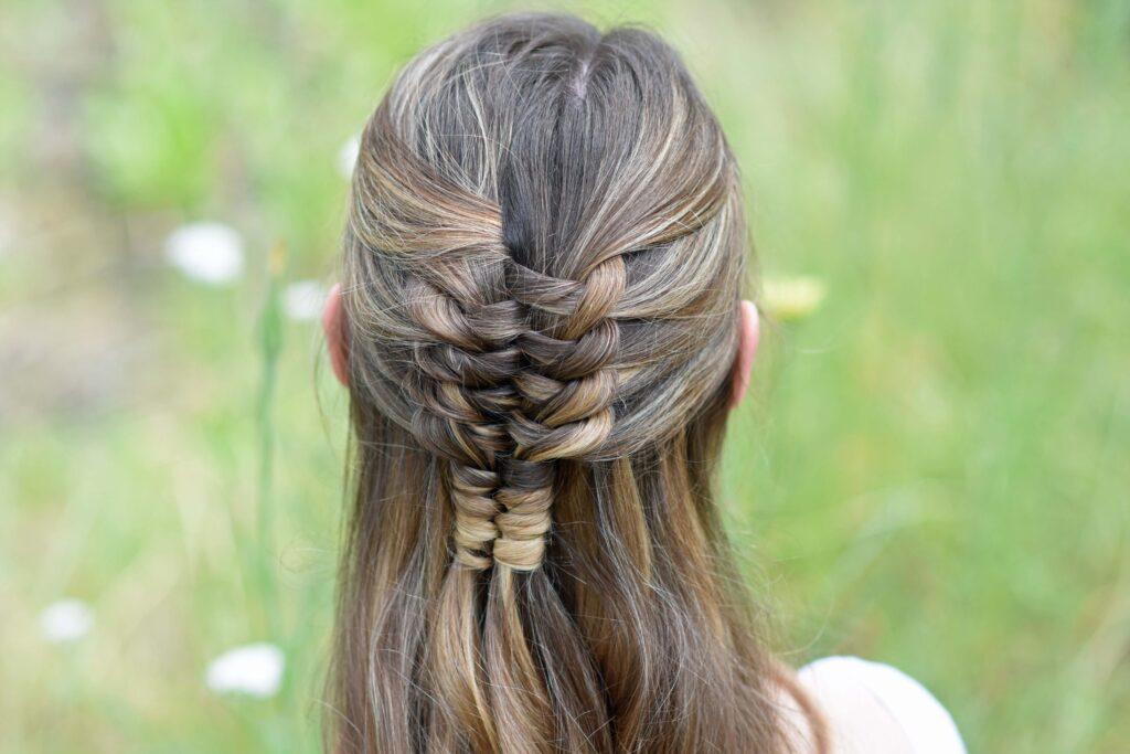 "Close up back view of young girl standing in a meadow modeling ""Floating Infinity Braid"" hairstyle"