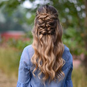 "Back view of young girl wearing a blue shirt standing outside modeling ""Twisted Fishtail"" hairstyle"