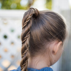 "Close-up back view of little girl standing outside modeling ""Twist Wrap Ponytail"""