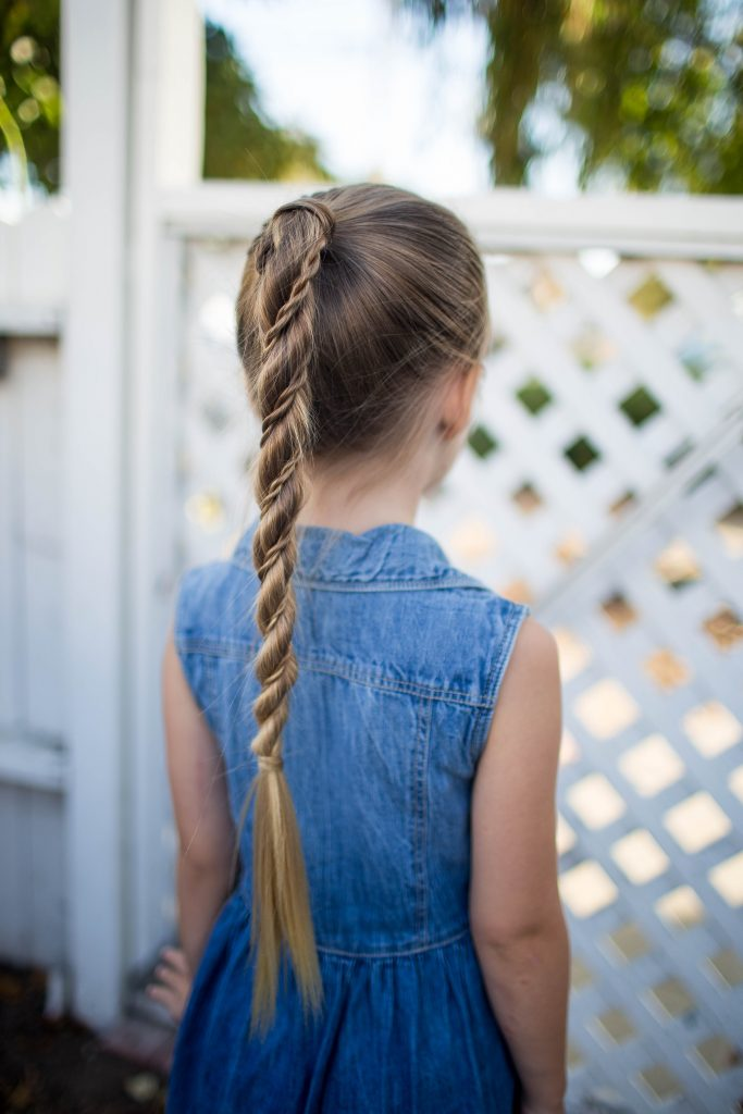 "Back view of little girl wearing a denim dress standing outside modeling ""Twist Wrap Ponytail"""