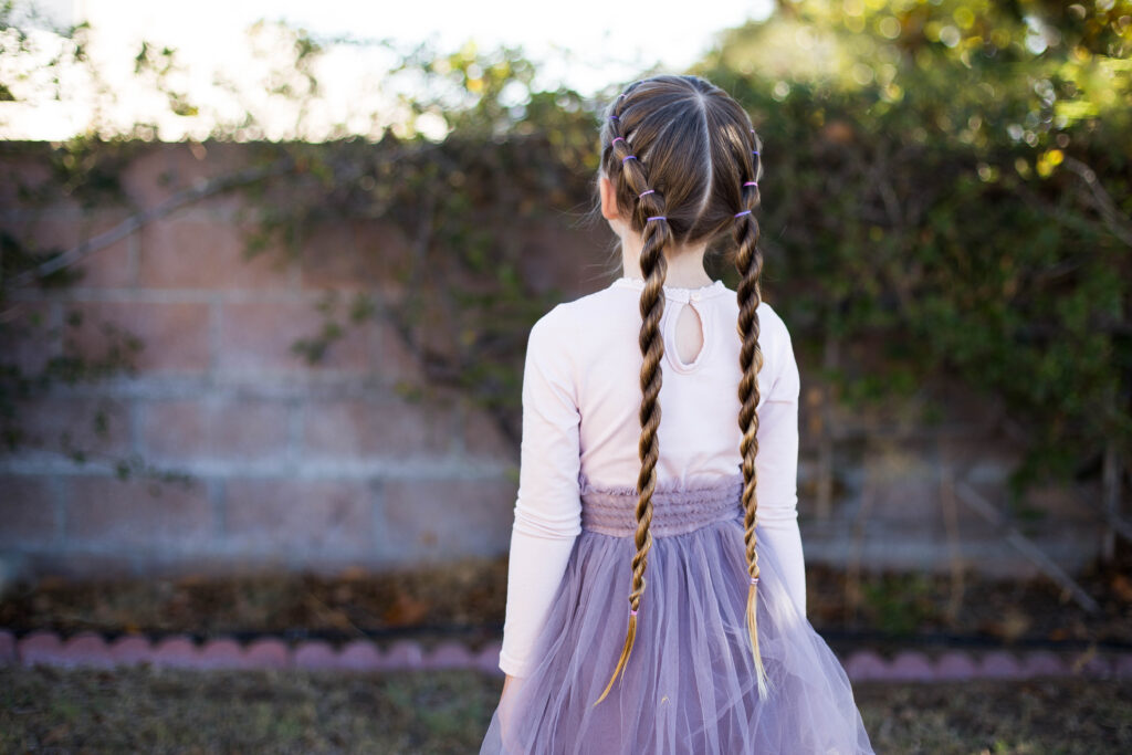 "Back view of little girl standing outside in her tutu modeling ""Banded Twist Braid"" hairstyle"