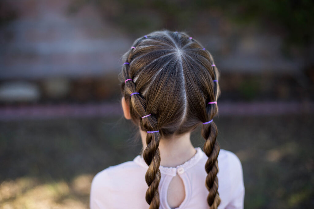 "Close up back view of little girl standing outside modeling ""Banded Twist Braid"" hairstyle"