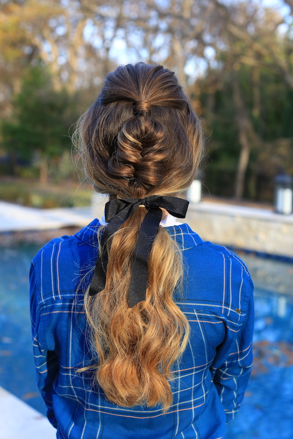 "Back view of girl standing outside wearing a blue shirt modeling ""Fishtail Ponytail"" hairstyle"