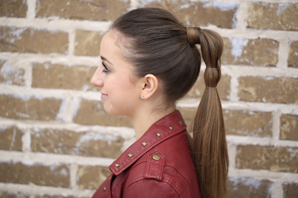 "Profile of girl standing outside in front of a brick wall wearing a red jacket modeling ""Heart Ponytail"" hairstyle"