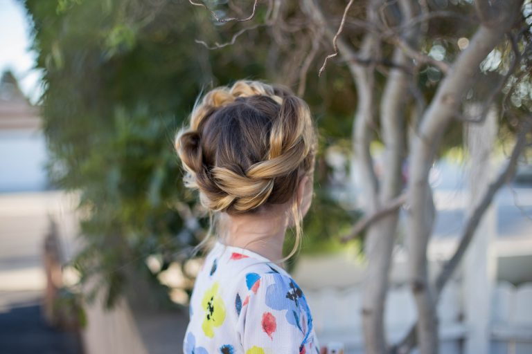 """Back view of young girl standing outside modeling """"Pull-Thru Crown Braid"""" hairstyle"""
