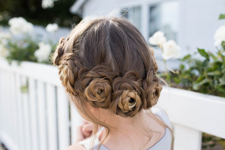 """Back view of young girl standing outside in front of white flowers modeling """"Flower Crown Braid"""" hairstyle"""