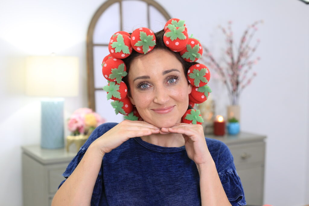Portrait of woman sitting indoors wearing 'Strawberry Foam Curlers' product in her hair