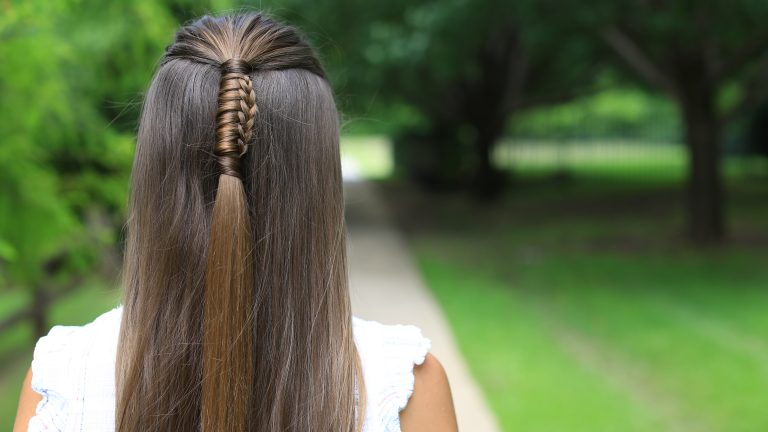 """Girl standing outside in the park wearing a white shirt modeling """"Reverse Chinese Ladder Braid"""" hairstyle"""