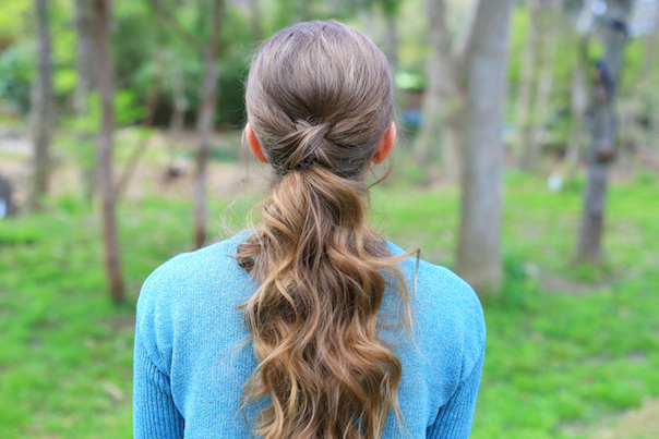"Back view of girl standing outside wearing a blue sweater modeling ""Criss Cross Ponytail"" hairstyle"