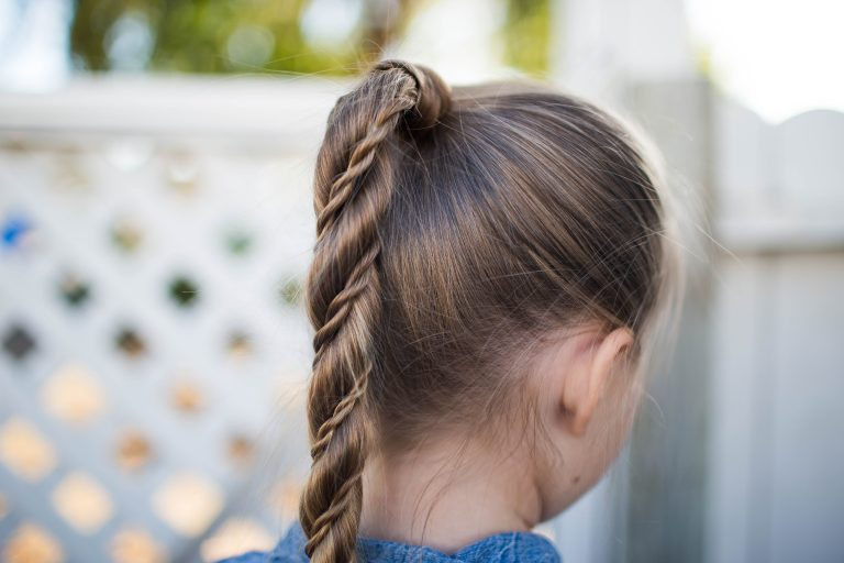 """Side view of girl standing outside modeling """"Twist Wrap Ponytail"""" hairstyle"""