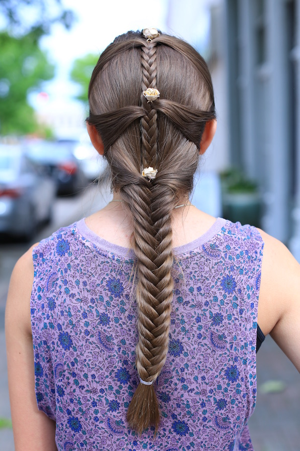 """Back view of girl standing outside with a purple shirt modeling """"Fishtail Mermaid Braid"""" hairstyle with flower accessories."""