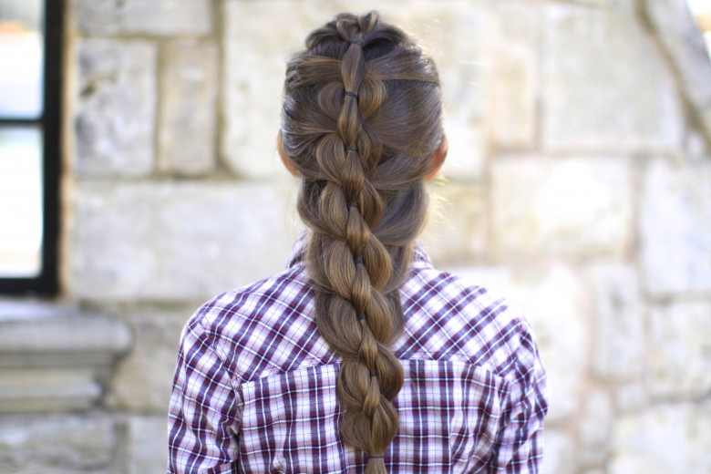 """Back view of girl with purple shirt standing outside modeling """"Pull-Through Mermaid Braid"""" hairstyle"""