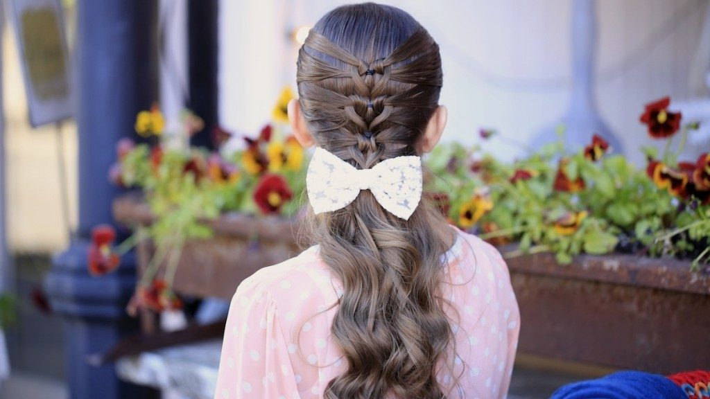 """Back view of girl with pink shirt standing outside in front of flower bed modeling """"Mermaid Heart Braid"""" hairstyle with a bow in her hair."""