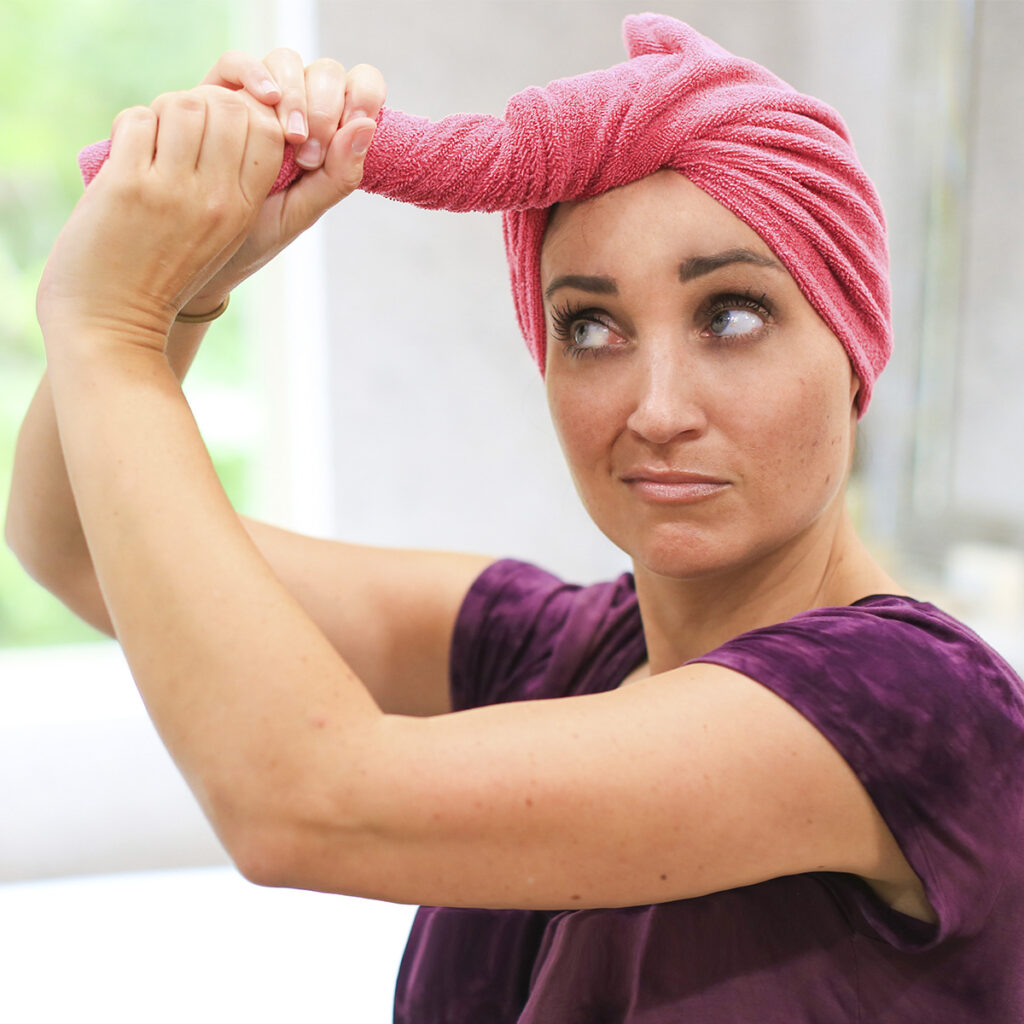 A woman twisting a towel to dry her hair