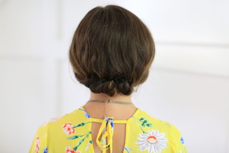 "Back view of girl standing in front of white background with a yellow shirt modeling ""Easy Rolled Updo"" Hairstyle"