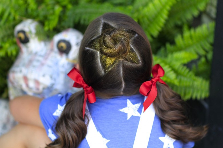 "Back view of young girl sitting outside in 4th of July attire modeling ""Star Bun Combo"" hairstyle"