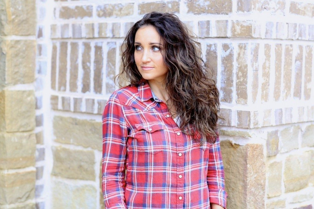 Woman with curling hair wearing a red plaid shirt standing outside in front of a brick background