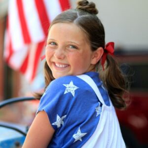 "Side view of smiling girl during 4th Of July celebration modeling ""Star Bun Combo"" hairstyle"