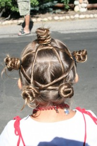 "Back view of young girl outside modeling ""Star Twist Buns"" hairstyle"
