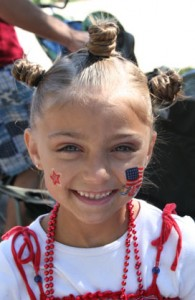 Young girl smiling outside in 4th Of July attire and stamps on her face