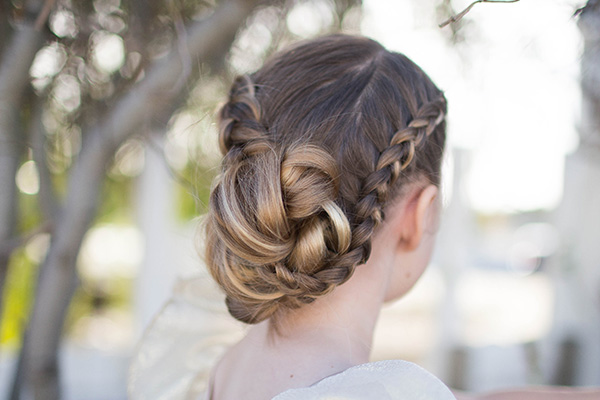 "Back view of young girl standing outside modeling ""Braided Bun Updo"" hairstyle"