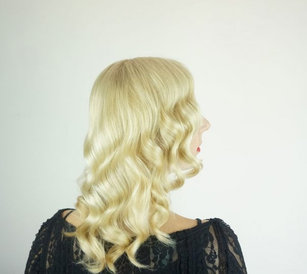 Back view of blonde woman wearing a black shirt in front of a white background wearing red lipstick