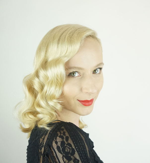 Blonde woman wearing a black shirt in front of a white background wearing red lipstick