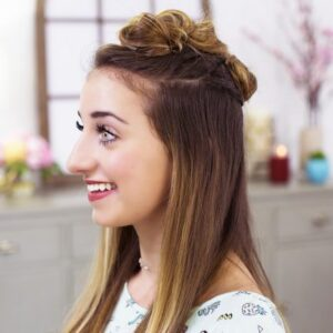 "Side view of a girl smiling sitting in her room modeling ""Triple Top Knot"" hairstyle"