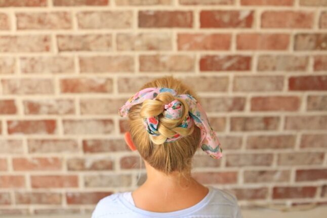 "Back view of girl with a white shirt in front of brick background modeling ""Braided Scarf Bun"" hairstyle"