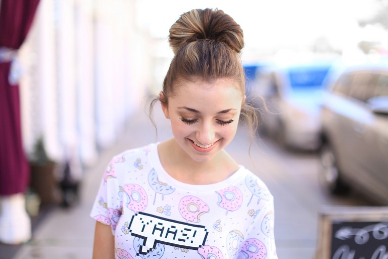 "Portrait of a girl smiling and looking down while standing outside modeling ""Double Fan Bun"""