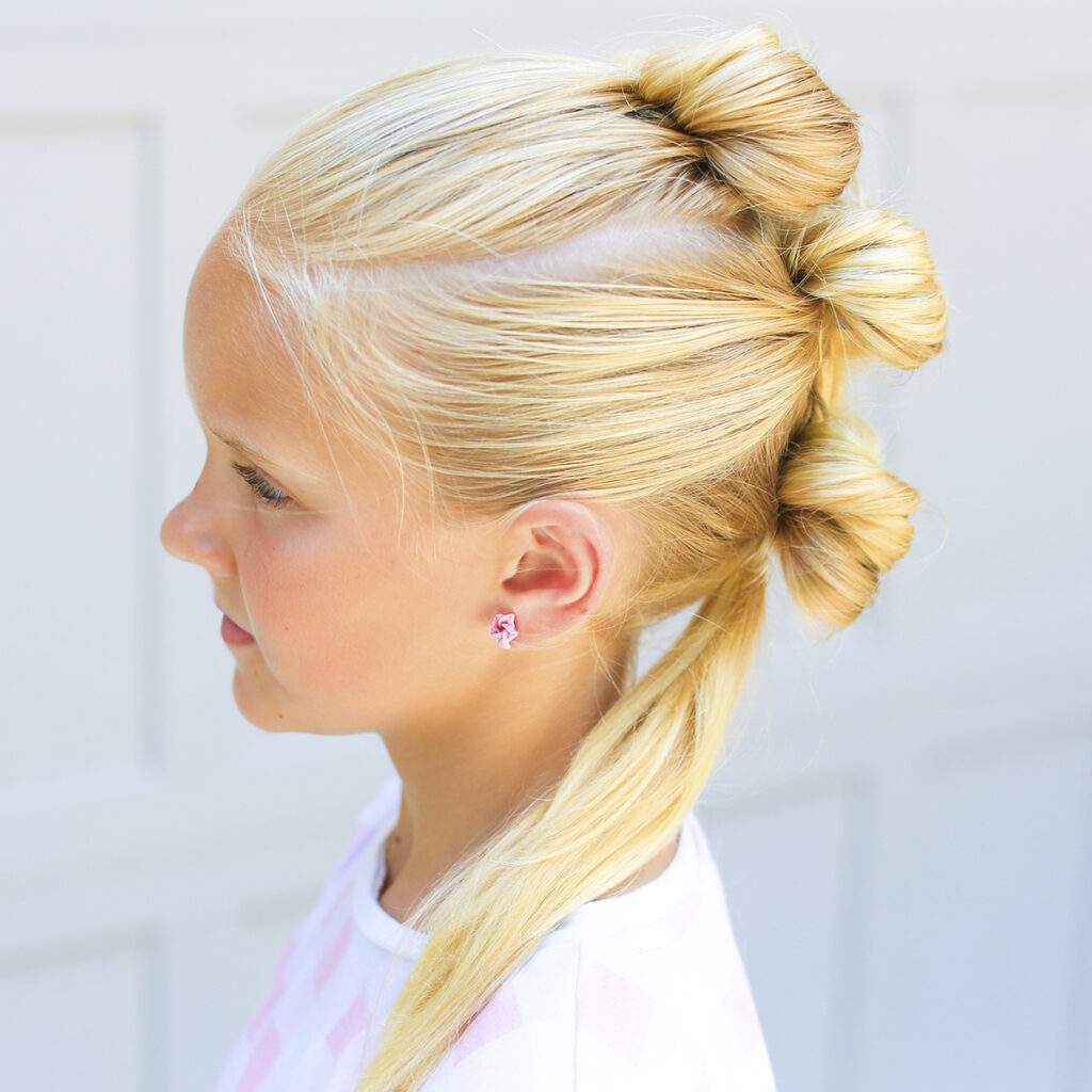 "Side view of blonde girl standing outside in front of a white background modeling ""Triple Bow Hawk"" hairstyle"
