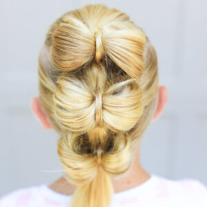 "Back view of blonde girl standing outside in front of a white background modeling ""Triple Bow Hawk"" hairstyle"