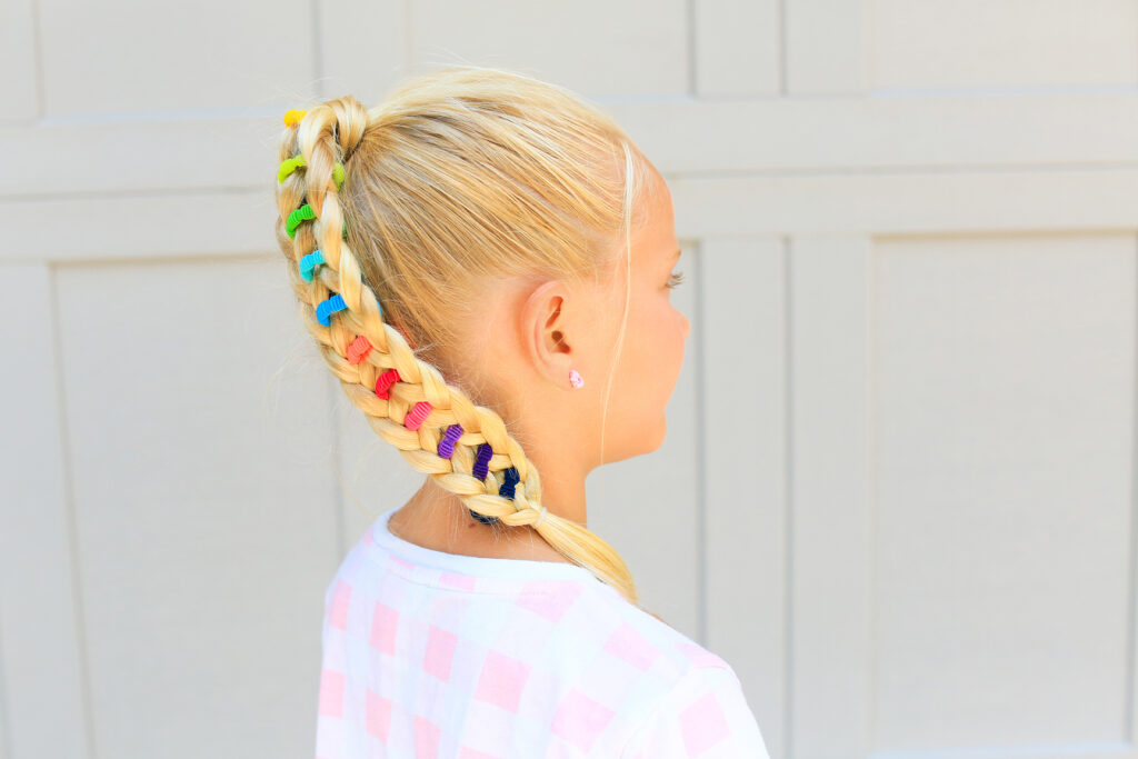 "Side view of young girl standing outside with a pink shirt modeling multicolor ""Banded Ponytail"" hairstyle"