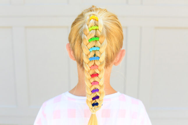 "Back view of young girl standing outside with a pink shirt modeling multicolor ""Banded Ponytail"" hairstyle"