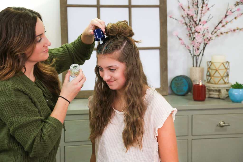 Mom with green shirt applying glitter glue to daughter's hair roots.