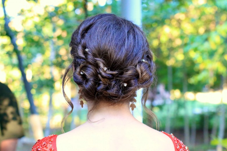 """Back view of girl standing outside modeling """"Rope Twist Updo"""" hairstyle."""