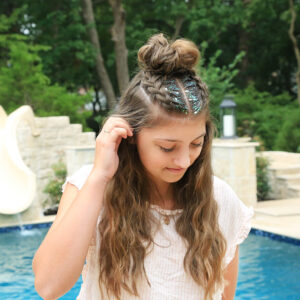 Girl standing by the pool with glitter in her hair modeling Double Dutchbacks into a Messy Bun hairstyle