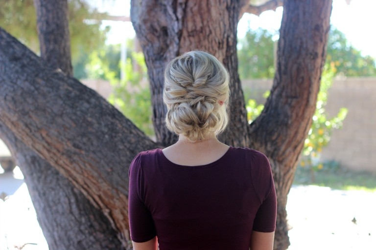 """Back view of girl with a purple shirt standing outside modeling """"Topsy Tail Bun"""" hairstyle."""