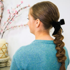 "Side view of girl standing indoors with a blue shirt modeling ""Wrapped Braid"" hairstyle with a black bow"