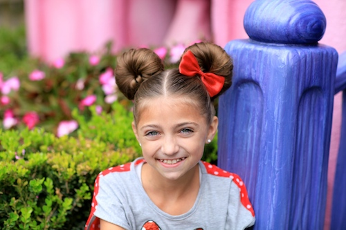 "Portrait of young girl smiling while sitting outside modeling ""Minnie Mouse Buns"" hairstyle with a red bow."