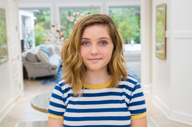 Portrait of girl smiling standing in her entryway wearing a blue striped shirt