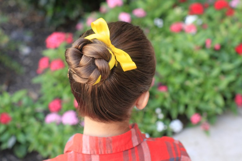 "Back view of girl standing outside in front of a bed of flowers with a yellow ribbon in her hair modeling ""Braided Bun with Ribbon"" hairstyle"